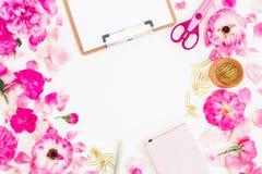 Espacio de trabajo rosado elegante con el tablero, el cuaderno, las flores color de rosa y los accesorios en el fondo blanco Ende Imagenes de archivo