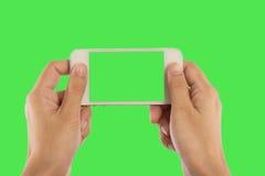 Espacio en blanco de la foto Las mujeres dan sostener el teléfono elegante móvil en blanco en gree Imagen de archivo libre de regalías