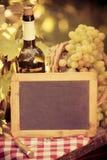Espacio en blanco de la pizarra, botella de vino y uvas de madera de la vid foto de archivo