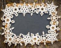 Espacio en blanco de la pizarra enmarcado en copos de nieve de madera Imagen de archivo