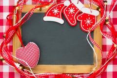 Espacio en blanco de la pizarra enmarcado en decoraciones rojas de la Navidad Fotos de archivo libres de regalías