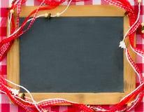 Espacio en blanco de la pizarra enmarcado en decoraciones rojas de la Navidad Imágenes de archivo libres de regalías