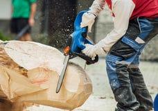 Espacio en blanco de madera de la manija del escultor con la sierra eléctrica Foto de archivo libre de regalías