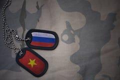 espacio en blanco del ejército, placa de identificación con la bandera de Rusia y Vietnam en el fondo de color caqui de la textur Imagen de archivo