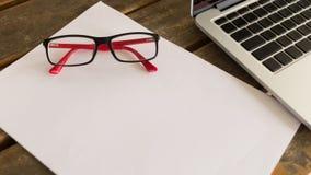 Espacio en blanco del Libro Blanco en la oficina de madera de la tabla con las lentes Fotografía de archivo