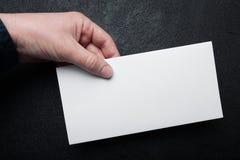 Espacio en blanco blanco estándar del sobre del correo a disposición en un fondo negro Mofa para arriba fotografía de archivo libre de regalías