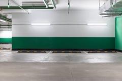 Espacio libre en el aparcamiento subterráneo con una pared verde imagenes de archivo