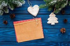Espacio para el saludo del Año Nuevo Juguetes cercanos de papel de la Navidad y ramas spruce en maqueta de madera azul de la opin Fotografía de archivo