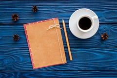 Espacio para el saludo del Año Nuevo Juguetes de la Navidad y cono cercanos de papel del pino en maqueta de madera azul de la opi Imagen de archivo