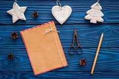 Espacio para el saludo del Año Nuevo Juguetes de la Navidad y cono cercanos de papel del pino en maqueta de madera azul de la opi Fotos de archivo