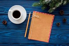 Espacio para el saludo del Año Nuevo Taza cercana de papel de café y de ramas spruce en maqueta de madera azul de la opinión supe Foto de archivo