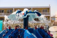 Espacio por la piscina con el patio de los ociosos y de los niños del sol con las diapositivas Piscina al aire libre para los niñ imagen de archivo