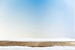 Espacio y tabla azules del fondo de Navidad con nieve Fotografía de archivo libre de regalías