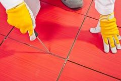 Espacios limpios de la herramienta sostenida entre los azulejos Fotografía de archivo libre de regalías
