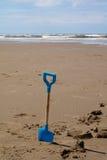 Espada azul de los childs en la playa con el mar en la distancia fotografía de archivo