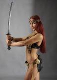Espada da terra arrendada da mulher em sua mão Foto de Stock