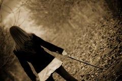 Espada del katana de la explotación agrícola de la mujer joven Fotografía de archivo libre de regalías
