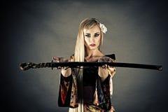 A espada do samurai da mulher dá Fotos de Stock
