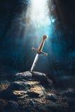 Espada en el excalibur de piedra Imagen de archivo libre de regalías