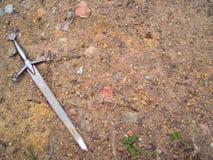 Espada en fondo de la suciedad de la grava Foto de archivo libre de regalías