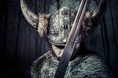 Espada, guerreiro de Viking com o capacete sobre o fundo da floresta Imagens de Stock