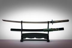 Espada japonesa del iaido en soporte de madera negro y el fondo blanco Imágenes de archivo libres de regalías
