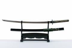 Espada japonesa del iaido en soporte de madera negro y el fondo blanco Fotos de archivo