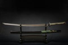 Espada japonesa del iaido en soporte de madera negro y fondo negro Foto de archivo