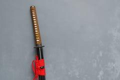 Espada japonesa do katana com fundo do concreto do sótão Fotos de Stock Royalty Free