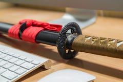 Espada japonesa do katana em uma tabela do computador na sala do escritório Fotos de Stock Royalty Free