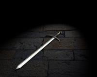 Espada medieval en la tierra pedregosa. Fotos de archivo