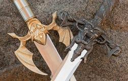 Espadas cruzadas medievales con los demonios Foto de archivo