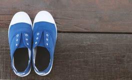 Espadrille bleue de plan rapproché sur le plancher en bois avec le ton, le sport ou le r de vintage Photos stock