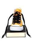 Espadrille jaune sur le livre noir Photo stock