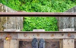 Espadrille noire sur le vieux chemin de fer en bois Photos libres de droits