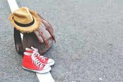 Espadrille rouge de sac de Brown avec le chapeau sur le fond de route Photo libre de droits