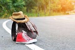Espadrille rouge de sac de Brown avec le chapeau sur le fond de route et de nature Photographie stock libre de droits