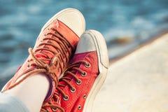 Espadrilles à la mode rouges sur la fille et paysage marin comme fond Image libre de droits