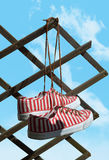 Espadrilles accrochant sur le ciel bleu Photographie stock libre de droits