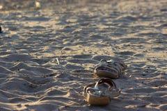 Espadrilles avec la vague de mer sur le fond de sable Image stock