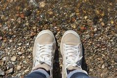 Espadrilles avec les dentelles blanches sur les pieds, l'eau et les pierres Photographie stock libre de droits