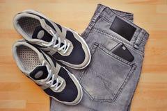 Espadrilles avec les jeans gris sur le fond en bois Photo stock