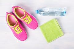 Espadrilles avec une serviette et une bouteille de l'eau pour des activités sportives, ensemble sur un beau fond Photo libre de droits