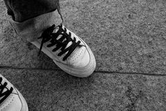 Espadrilles blanches avec les dentelles noires sur leurs pieds sur le plancher en pierre Photographie stock