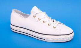Espadrilles blanches d'isolement sur le fond bleu Chaussures de sport avec le chemin de coupure Photo libre de droits