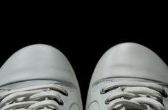 Espadrilles blanches d'isolement sur un fond noir Images stock