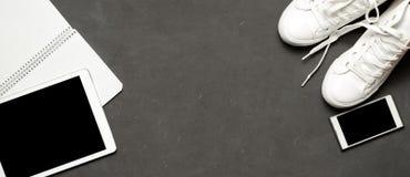 Espadrilles blanches de bannière occasionnelle élégante sur le fond noir avec le téléphone, écouteurs, comprimé, livre de copie Images stock