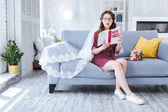Espadrilles blanches de port de future épouse se reposant sur le sofa gris Photographie stock libre de droits