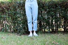 Espadrilles blanches occasionnelles de hippie Chaussures de femelle et pantalon blancs de port debout de blues-jean sur le fond d Photos stock