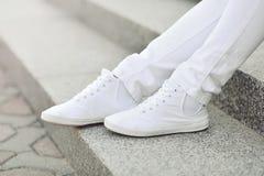 Espadrilles blanches sur des jambes de fille  Images libres de droits